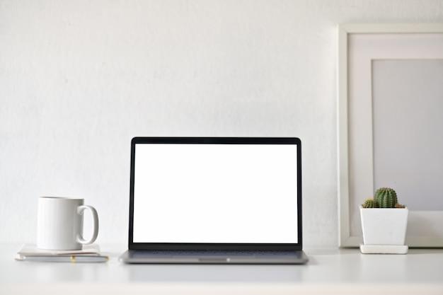 Lege witte het schermlaptop met bureaulevering op witte bureauwerkruimte.