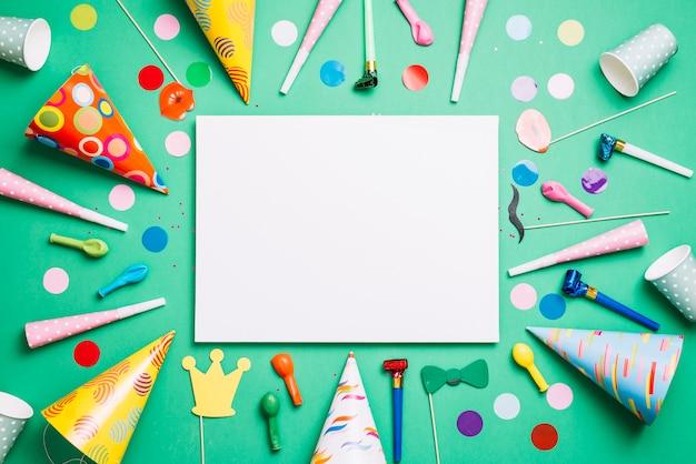 Lege witte kaart versierd met verjaardagsartikelen en confetti op groene achtergrond