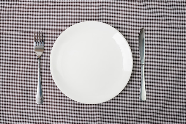 Lege witte keramiek plaat met mes en vork op tabelachtergrond. eet- en keukengerei concept