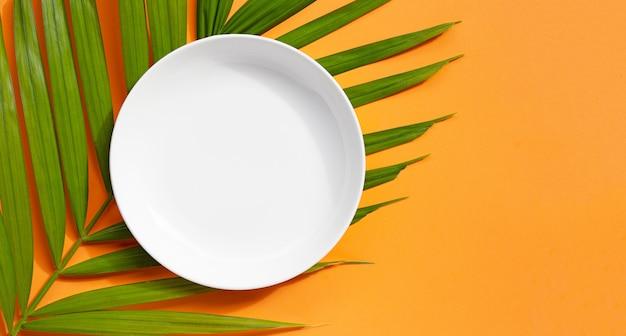 Lege witte keramische plaat op tropische palmbladeren op oranje achtergrond.