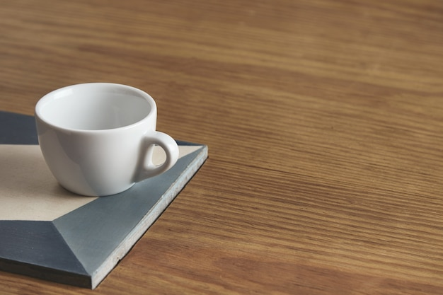 Lege witte koffiekopje op keramische plaat op dikke houten tafel in caféwinkel.