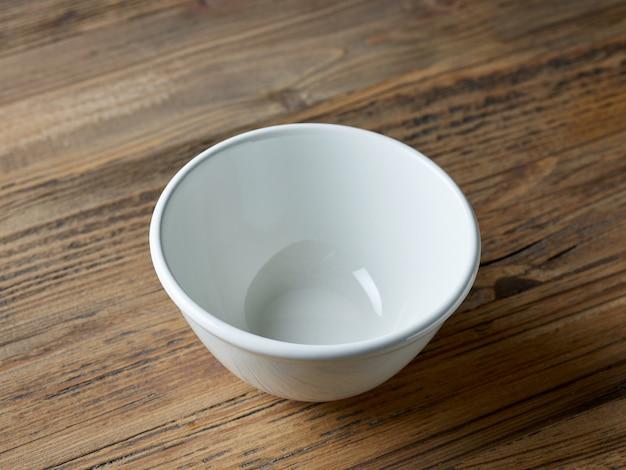 Lege witte kom op houten keukentafel