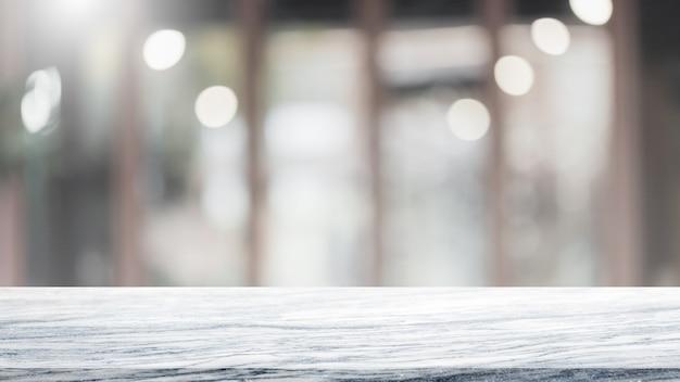 Lege witte marmeren stenen tafelblad en vervagen glazen venster interieur café