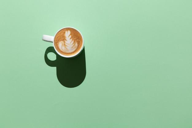 Lege witte mok met cappuccino, latte art in hard licht op pastelgroene tafel, bovenaanzicht