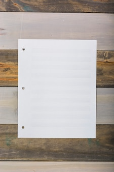 Lege witte muzikale pagina geplakt op houten muur