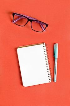 Lege witte notebook, bril en pen op oranje en groene achtergrond. minimalistisch concept met plaats voor tekst. bespotten met decorelementen.