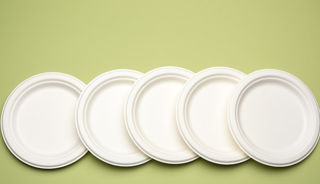 Lege witte papieren wegwerp borden op een groene achtergrond, bovenaanzicht. het concept van afwijzing van plastic, milieubehoud