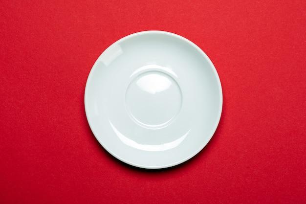 Lege witte plaat die op rode oppervlakte wordt geïsoleerd