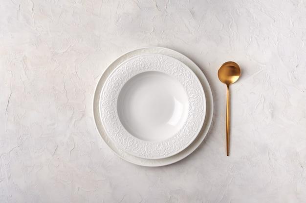 Lege witte plaat en gouden lepel keukengerei op een lichtgrijs tafelblad, plat gelegd met