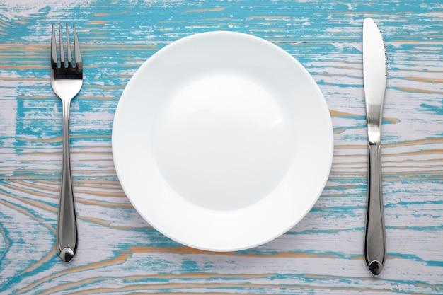 Lege witte plaat met zilveren vork en mes op blauwe houten tafel. diner plaats instelling. bovenaanzicht