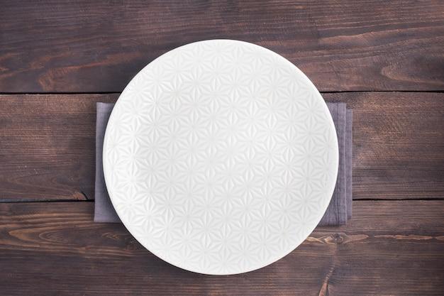 Lege witte plaat op houten rustieke tafel. bovenaanzicht met kopie ruimte.