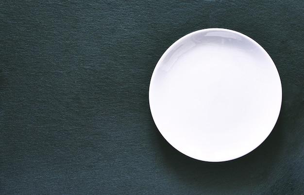Lege witte plaat op zwart leisteen bord