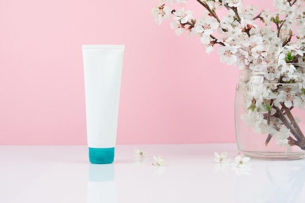Lege witte plastic buis biologische natuurlijke huidverzorgingsproducten en bloem. verpakking van lotion, crème of serumcosmetica