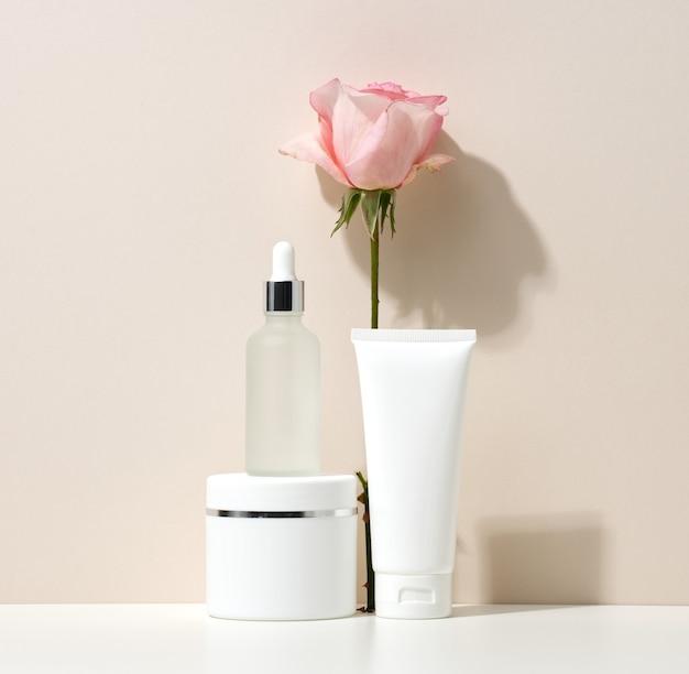 Lege witte plastic buizen en potten voor cosmetica. verpakking voor crème, gel, serum, reclame en productpromotie, mock-up