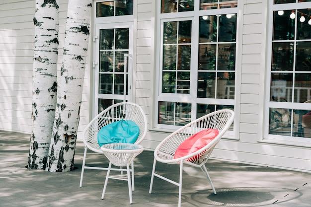 Lege witte tafels buiten restaurant café stoel met gekleurde kussens op stoep straat buitenshuis