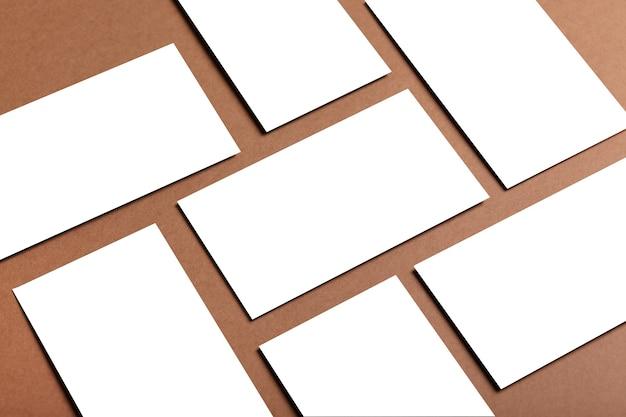 Lege witte uitnodigingskaart of visitekaartjemodel op een bruine tafel