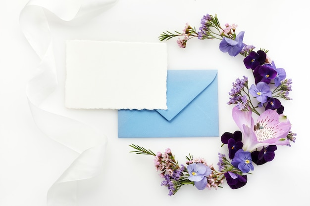 Lege witte wenskaart en envelop met paarse wilde bloemen op witte achtergrond voor creatief werkontwerp. plat leggen