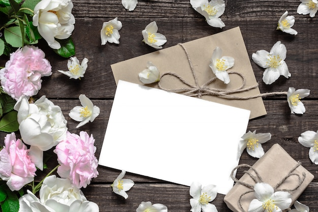 Lege witte wenskaart met roze en witte rozen in frame gemaakt van jasmijnbloemen met geschenkdoos
