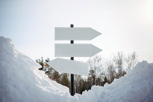 Lege witte wijzers, wegwijzer tegen de achtergrond van de de winteraard. richtingpijltekens op paal in besneeuwd bos. kerstmis en nieuwjaar concept.