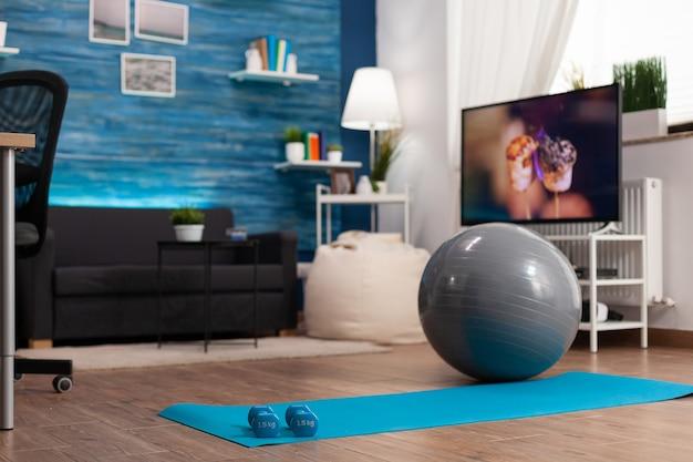 Lege woonkamer met niemand erin klaar voor fitnesstraining met yogamat en dumbells
