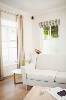 Lege woonkamer met sofa en tafel met krant en televisie op afstand