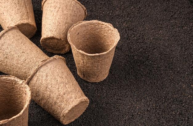 Lege zaailingenpotten zijn verspreid over het zijaanzicht van de grond met kopie ruimte