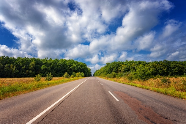 Lege zomersnelweg in een heuvelachtig gebied, tegen de achtergrond van blauwe lucht en witte wolken, met weilanden en bomen aan de zijkanten