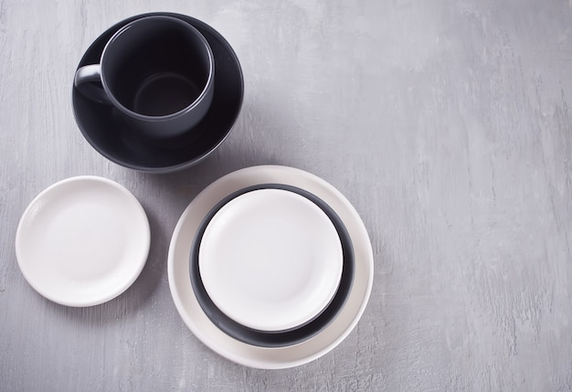 Lege zwart-witte platen over grijze tafel.