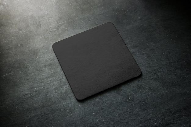 Lege zwarte bierviltje die op grijs bureau ligt