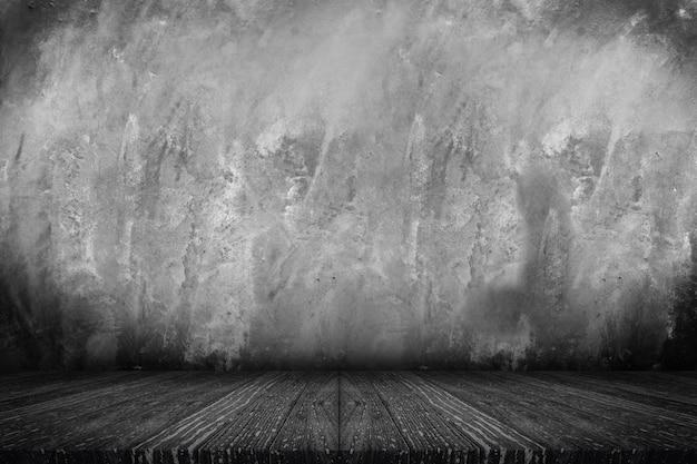 Lege zwarte houten plank tafelblad met grunge betonnen muur