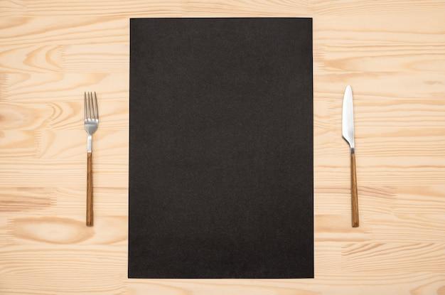 Lege zwarte kaart a4, a3 en bestek op houten tafel. bovenaanzicht zwarte receptenpapierpagina