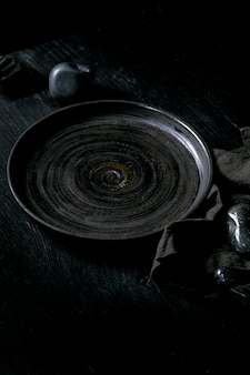 Lege zwarte keramische plaat met zwarte stenen rond op textiel servet over zwarte houten achtergrond.