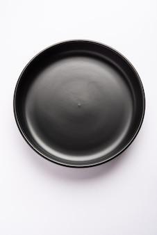 Lege zwarte keramische serveerschaal, geïsoleerd over wit of grijs oppervlak