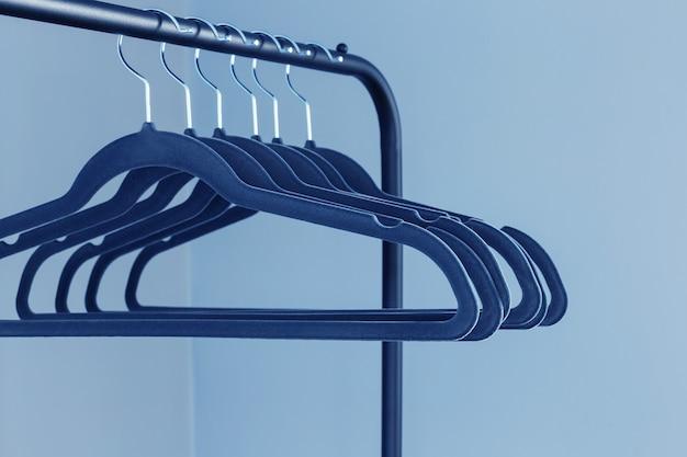 Lege zwarte kleerhanger op blauwe muurachtergrond