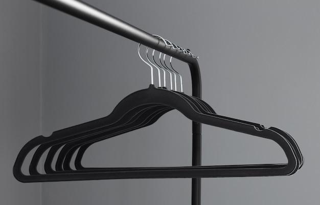 Lege zwarte kleerhanger op grijze muurachtergrond