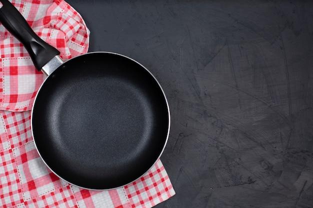 Lege zwarte koekenpan met keuken handdoek op zwarte tafel.