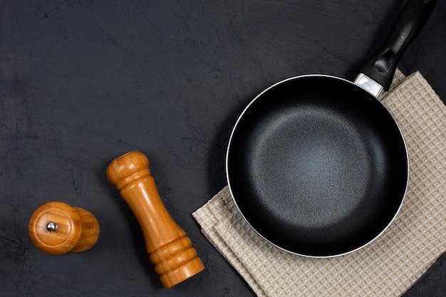 Lege zwarte koekenpan of koekepan met peper en zeezout