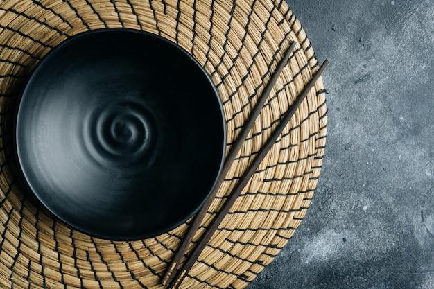 Lege zwarte kom (met de hand gemaakt ceramisch) met chinese eetstokjes op een grijze steen