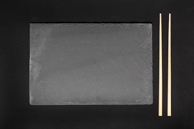 Lege zwarte leisteen lade plaat en eetstokjes op zwarte achtergrond.
