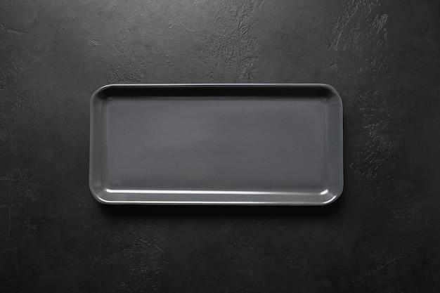 Lege zwarte moderne rechthoekige plaat op zwarte achtergrond, keuken spullen, plat leggen voor koken als achtergrond.