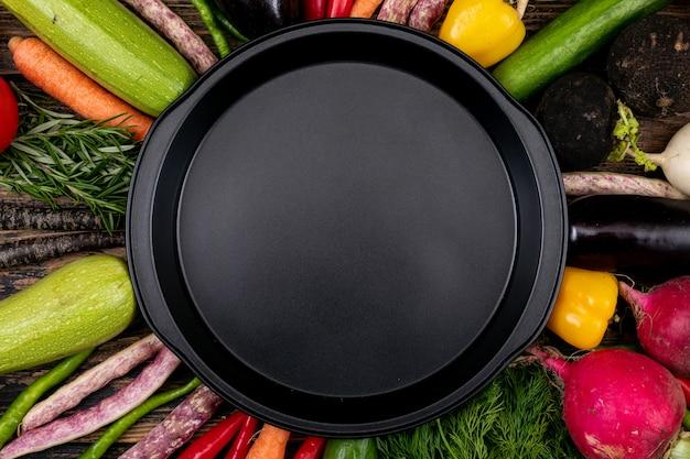 Lege zwarte pan met verse groenten rond