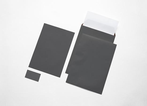 Lege zwarte papieren enveloppen, briefpapier en kaart geïsoleerd op wit. 3d-afbeelding.