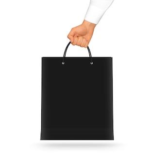 Lege zwarte papieren zak mock up in de hand houden