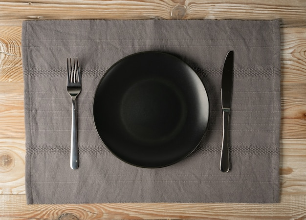 Lege zwarte plaat en bestek op houten tafelblad weergave met kopie ruimte.
