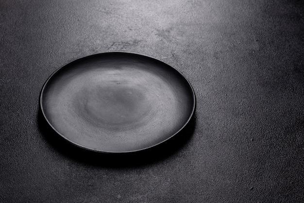 Lege zwarte plaat over donkere stenen tafel