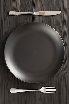 Lege zwarte plaat serveert houten tafel