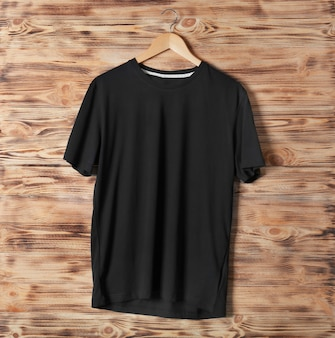 Lege zwarte t-shirt tegen houten muur