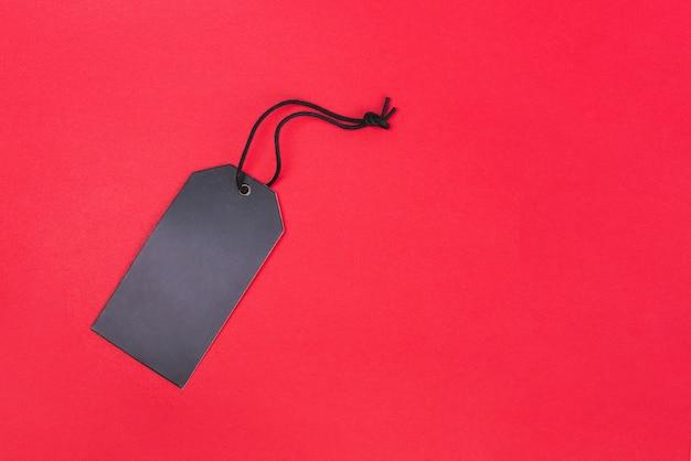 Lege zwarte tag op rode achtergrond met kopie ruimte. prijskaartje, cadeau-tag, verkoop tag, adres label