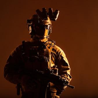 Leger elite krachten lid, moderne infanterist met verborgen gezicht, in tactische munitie, uitgeruste radioheadset, nachtzichtapparaat gemonteerd op helm, staande met korte loop dienstgeweer in handen