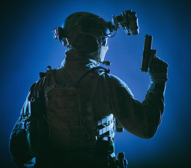 Leger elite krachten soldaat, politie speciale operatie, contraterroristische teamlid in tactische munitie met verborgen achter maskeridentiteit, achteruit staand met pistool in de hand, low key studio shoot